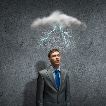 Young businessman looking above at raining sky photo