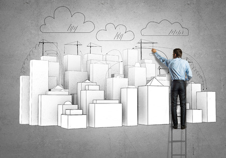 Rear view of businessman standing on ladder and drawing buildings photo