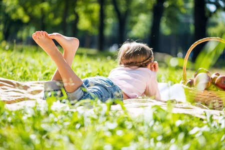 Rear view of little girl lying in summer park photo