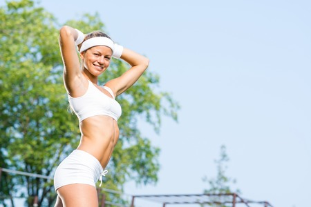 Young sport woman enjoying weather in sunny park photo