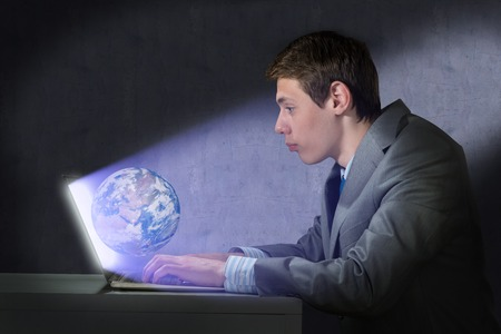 businessman with a laptop, the light on the face from the screen photo