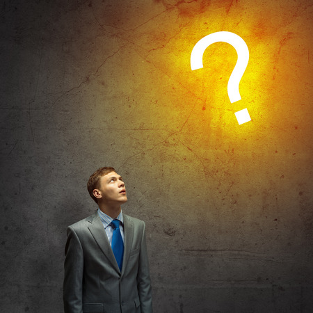 Young businessman looking thoughtfully at question mark photo