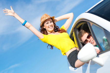 young attractive woman in sunglasses got out of the car window and laugh photo