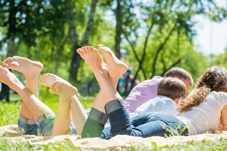 Young happy family lying in park barefoot photo