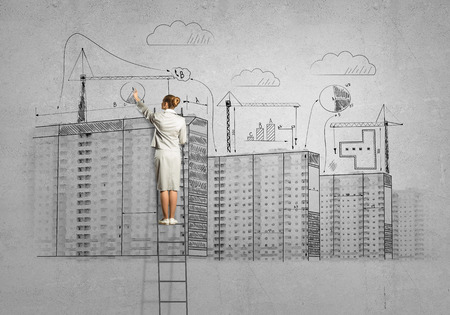 Rear view of businesswoman standing on ladder and drawing on wall photo
