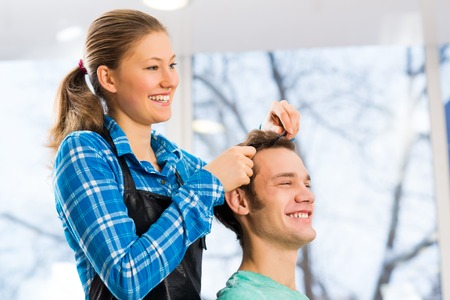 haircutter: young attractive woman hairdresser hairstyle customer picks Stock Photo