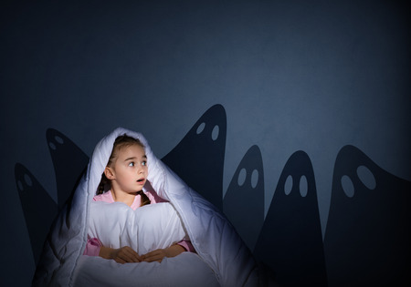 bad girl: image of a girl under the covers with a flashlight the night afraid of ghosts Stock Photo