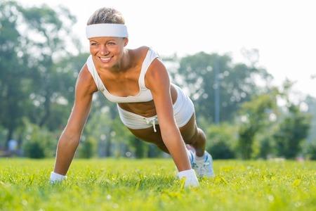 sport wear: Mujer joven en el deporte desgaste haciendo flexiones en el parque