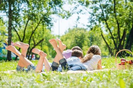 familia picnic: Familia feliz joven acostada en el parque de los pies descalzos