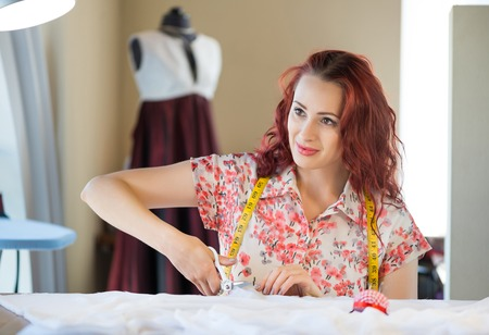 needlewoman: Young pretty needlewoman cutting fabric with scissors Stock Photo