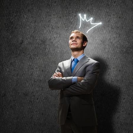 arroganza: Giovane uomo d'affari bello con corona sopra la sua testa
