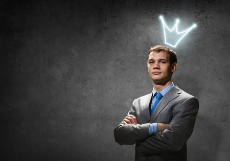 Young handsome businessman with crown above his head Stock Photo