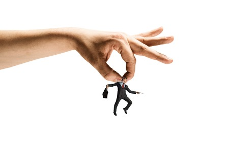 Close up of human hand catching miniature of businessman isolated on white photo