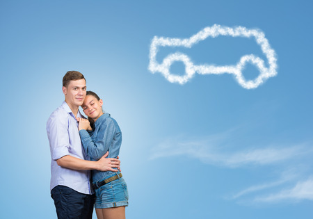 Young couple against sky background hugging each other photo