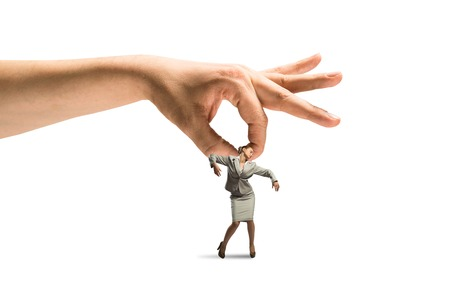 Close up of human hand catching miniature of businesswoman isolated on white photo