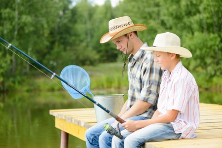 Father and son sitting on bridge and fishing photo
