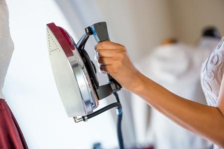 Close up de couturière femme avec le fer à la main