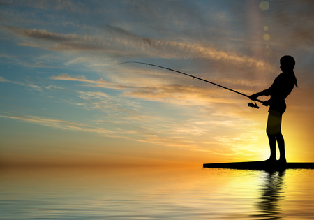 Silhouette of teenager girl fishing at sunset photo