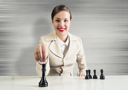 Young pretty businesswoman sitting at table and playing chess photo