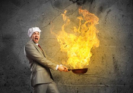 Jonge man in pak en kok hoed bedrijf pan Stockfoto