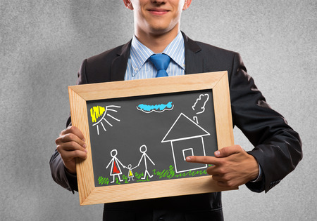 Close up of businessman holding chalkboard with family sketches photo