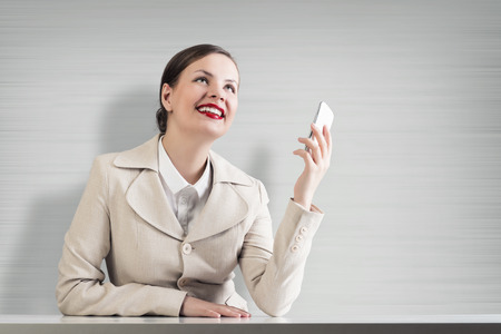Young pretty businesswoman sitting at table with mobile phone in hand photo
