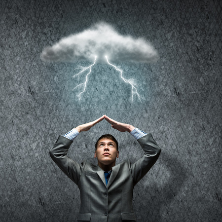 Young businessman under rain protecting head with arms photo
