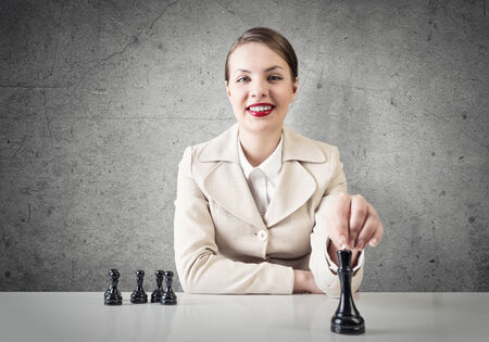 Smiling pretty woman sitting and playing chess photo