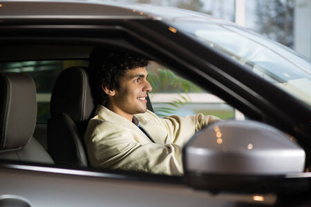 show room: Young handsome man at show room sitting in car Stock Photo