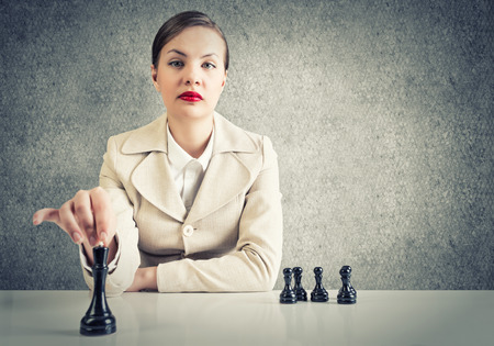 Serious pretty woman sitting and playing chess photo