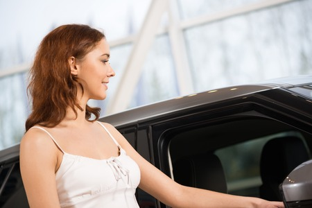show room: Young attractive woman in show room standing near car