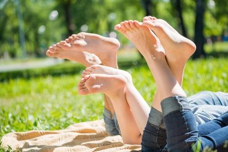 Junge glückliche Familie im Park liegend barfuß Lizenzfreie Bilder