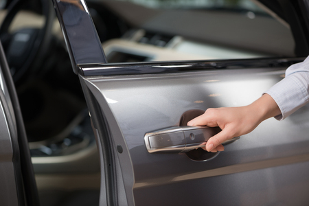 Close up of human female hand opening car door photo