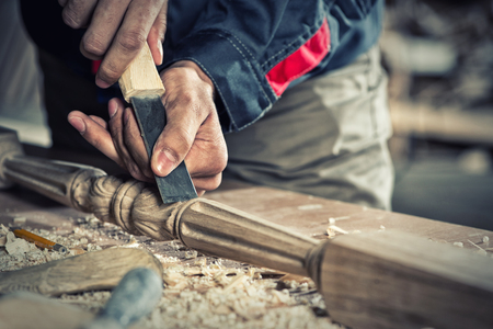 carpentry tools: Close up carpenters hands that work with cutter Stock Photo