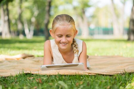 Cute girl lying in park and using tablet pc photo