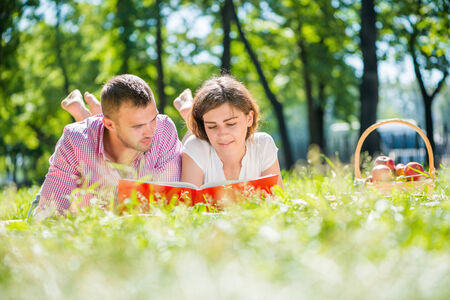 Young romantic couple lying in park and reading book photo