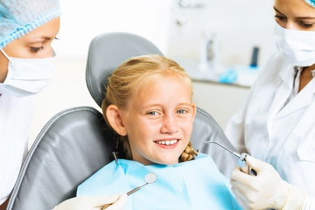Little cute girl sitting in chair at dentist photo