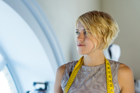 modiste: Young blonde needlewoman at studio with tape on neck Stock Photo