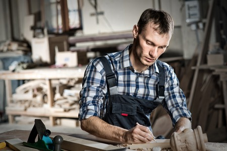 carpenter's sawdust: Young craftsman in uniform working at carpentry Stock Photo