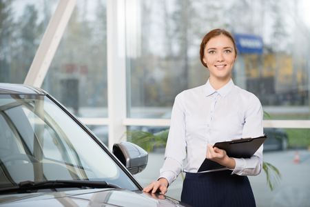 show room: Young woman consultant in show room standing near car