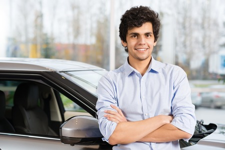 show room: Young handsome man at show room standing near car