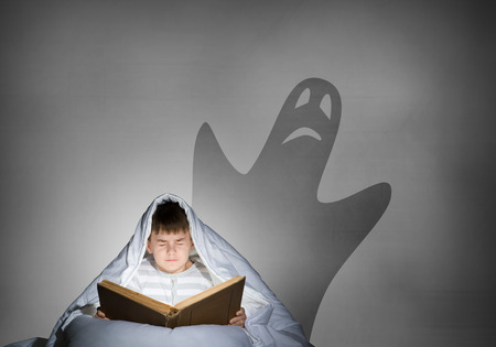 tremble: Cute boy in bed reading book under blanket