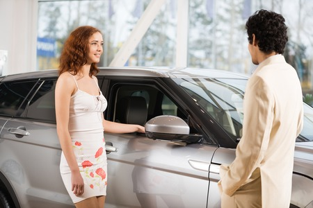 show room: Young woman in car show room talking with consultant Stock Photo