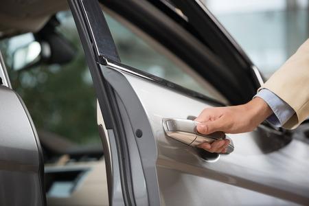 車のドアを開く人間の男性の手のクローズ アップ