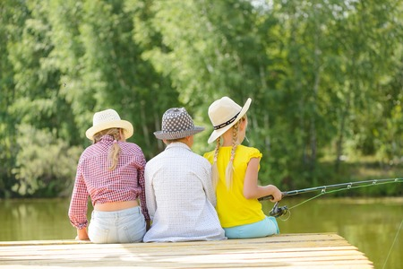 Back view of three children sitting on wooden pier with rod photo