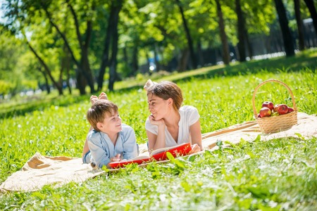 individually: Cute boy and young woman in summer park laying on grass