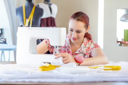 modiste: Young attractive needlewoman at studio working with sewing machine
