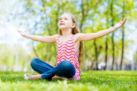 Girl in the park sitting on the grass and spread her arms photo