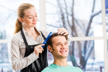 men and women: young attractive woman hairdresser hairstyle customer picks Stock Photo