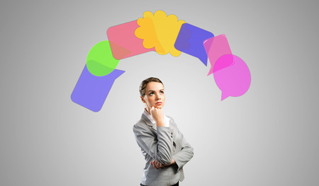 above head: Young thoughtful businesswoman and colorful speech bubbles above head Stock Photo